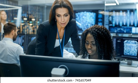 Female Team Leader Consults Young Computer Engineer. They Work in a Crowded Office on a Neural Network/ Artificial Intelligence Project.