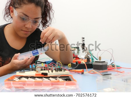 Female tech student learning how to wire a prototype circuit board