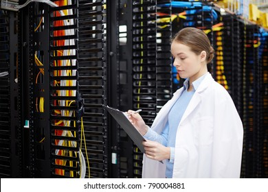 Female technician or expert in whitecoat making working notes in data center