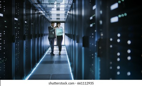 Female IT Technician and Male Server Engineer Talk and Discuss. They are in Working Data Center full of Rack Servers. Woman Holds Laptop.