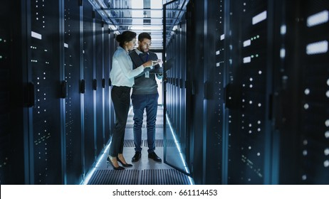 Female IT Technician and Male Server Engineer Talk and Discuss Settings of a Working Data Center. Man Holds Laptop.