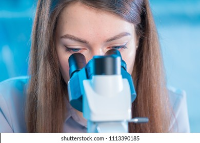 Female technician with a microscope in the laboratory
