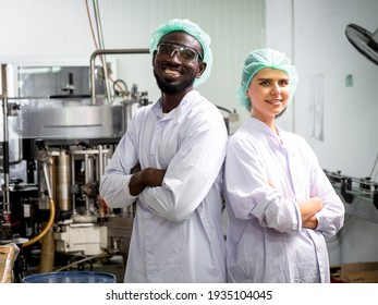 Female technician supervisor and male factory technicians work a machine control panel together in beverage factory production line
