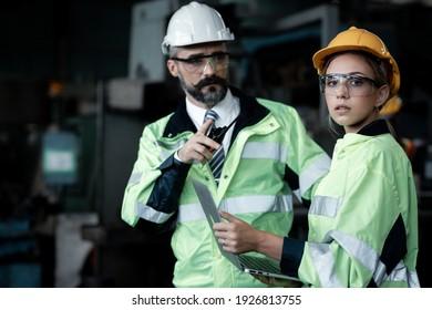 Weibliche Technikerin, die einen harten Hut, Schutzbrille und Sicherheitshemd trägt, hört der Aufgabe zu, während sie den Computer in der Maschinenfabrik benutzt.