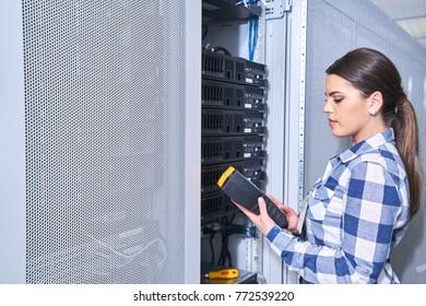 female technician working on server maintenance in white server room next to open server rack