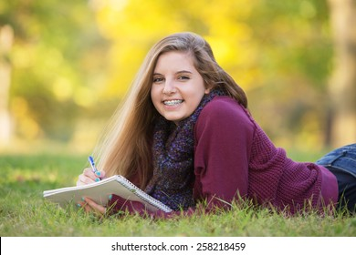 Female teen with braces taking notes while laying on ground