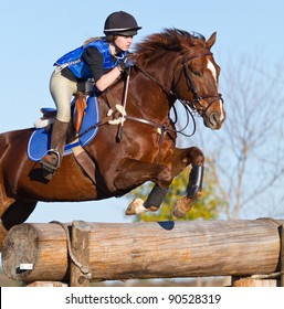 Female teen on cross country course jumps a horse over an obstacle