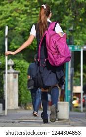 Female Teen Student With Bookbag Walking On Sidewalk