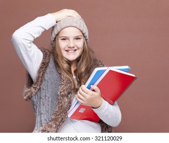 Female teen student carring notebooks against brown background