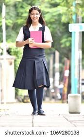Female Teen Student Standing On Sidewalk