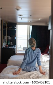 Female teenager enjoying watching sunrise from cabin luxury cruise ship. The concept of meeting the dawn on a cruise ship. Travel, sea, cruise