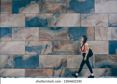 Female teenager student with backpack passing urban setting wall on street with copy space for advertising or text messages, young hipster girl in casual trendy outfit walking near publicity area