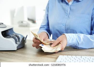 Female teller counting money at cash department, closeup