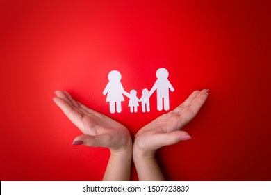 Female tender hands with a family symbol cut out of white paper. Protecting the rights of people and  minorities. Love for the children of the world on earth, a clean ecology. View from above.