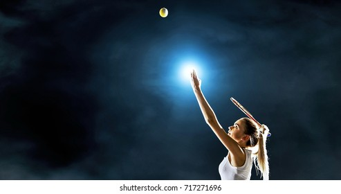 Female tennis player in action during game on the dark backgrounde. She is wearing unbranded sport clothes. The background is made in 3D.