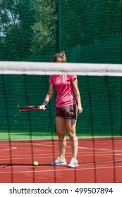 Female tennis player bouncing tennis ball on a court