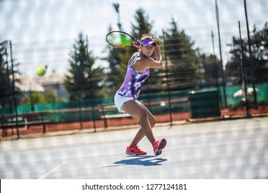 Female tennis player hits the ball with Backhand slice.