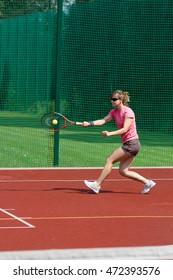 Female tennis player hitting forehand.
