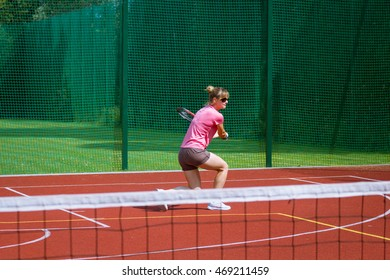 Female tennis player hitting a two-handed backhand