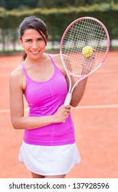 Female tennis player holding a racket at the court