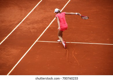Female tennis player making a setback on clay tennis court