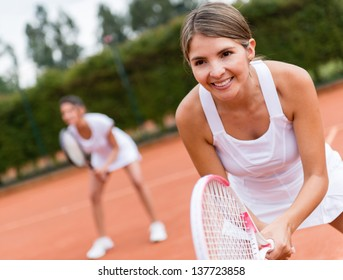 Female tennis players playing doubles and looking happy