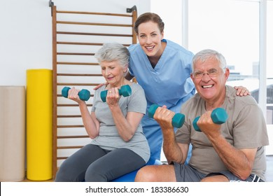 Female therapist assisting senior couple with dumbbells in the medical office