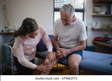 Female therapist examining knee of senior male patient at hospital ward