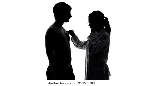 Female therapist examining male patient chest with stethoscope, health care