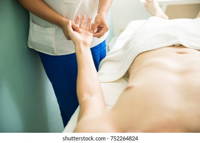 Female therapist giving a hand massage to a young man in a health spa