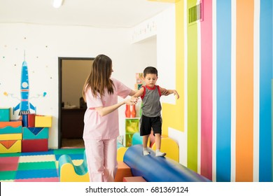 Female therapist helping a kid to maintain balance while walking on a beam in a therapy center