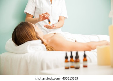 Female therapist holding a bottle with bach flower treatment for a client at a health clinic and spa