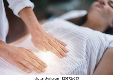Female therapist performing Reiki therapy treatment holding hands over woman's stomach. Alternative therapy concept of stress reduction and relaxation.