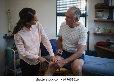 Female therapist pointing at knee while talking with senior male patient in hospital ward