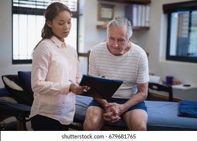 Female therapist showing clipboard to senior male patient sitting on bed at hospital ward