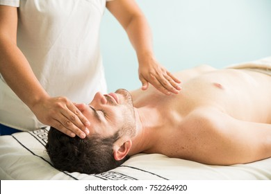 Female therapist using her hands for some reiki therapy on a young man in a holistic spa