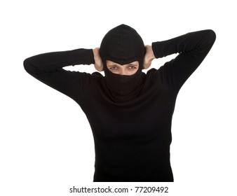 female thief in black clothes and balaclava with hands on ears