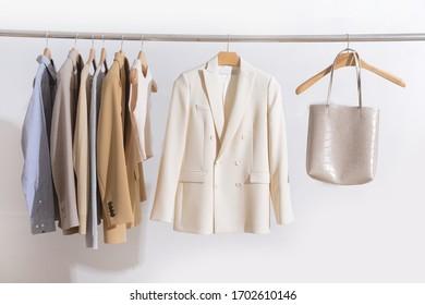 weibliche, dreistellige Business-formelle Jacke mit langärmeliger Baumwolle, grauem T-Shirt, Weste und weißer Handtasche auf Hängen