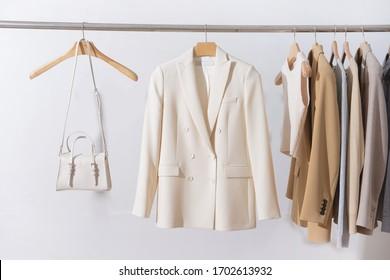 weibliche, dreistellige Business-formelle Jacke mit langärmelndem T-Shirt aus Baumwolle, Weste und Weiß-Handtasche am Hängen