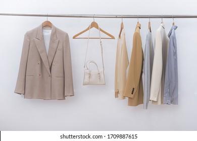 weibliche, dreistellige, formelle Jacke mit langärmeliger Baumwolle, Pullover und weißer Handtasche am Hängen