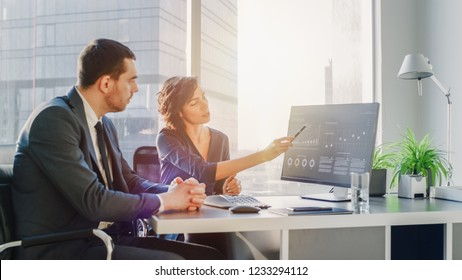 Female Top Manager and Male Businessman Sitting at the Desk Having Discussion and Working on a Desktop Computer, Solving Problems. Successful People in Modern Stylish Office with Big City Busines View