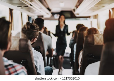 Female Tour Service Employee at Work on Tour Bus. Young Smiling Woman Standing between Passenger Seats of Touristic Bus. Traveling, Tourism and People Concept. People on Trip. Summer Vacation