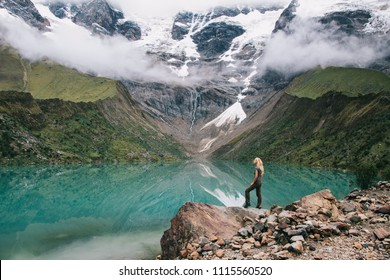 Female tourist in active wear admiring beauty scenery of amazing nature during hiking trek in Salkantay.Young woman traveller enjoying exciting mountains covered white clouds and recreation of trip