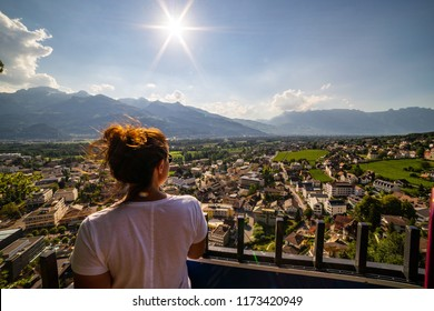 Female tourist admiring view of Vaduz, Liechtenstein. Vaduz is the capital of Liechtenstein and also the seat of the national parliament.