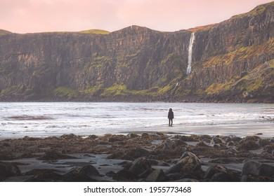 A female tourist alone in nature visits the coastal landscape at Talisker Bay Beach and the seaside Talisker Waterfall at sunset or sunrise on the Isle of Skye, Scotland