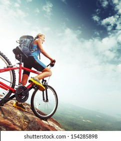 Female tourist with backpack and bicycle enjoying valley view from top of a mountain