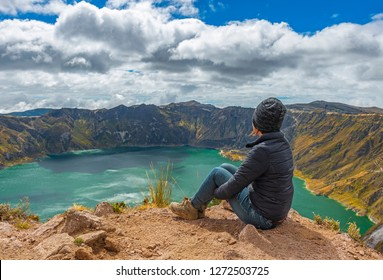 Female tourist and backpacker looking at the turquoise waters of the active Quilotoa crater lake during the Quilotoa Loop hike near the city of Quito, Ecuador.
