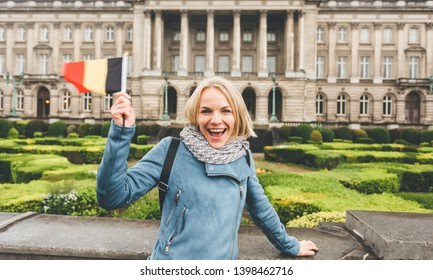 A female tourist in a blue jacket stands with the flag of Belgium against the background of one of the main attractions of the city - the Royal Palace in Brussels and smiles. Woman traveler enjoys