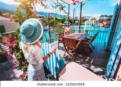 Female tourist with blue sun hat staying in Assos village in front of cozy veranda and admiring turquoise colored bay of Mediterranean sea and beautiful colorful houses of in Kefalonia, Greece