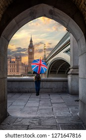 Female tourist with a british flag umbrella stands in front of the Big Ben clocktower in London, United Kingdom